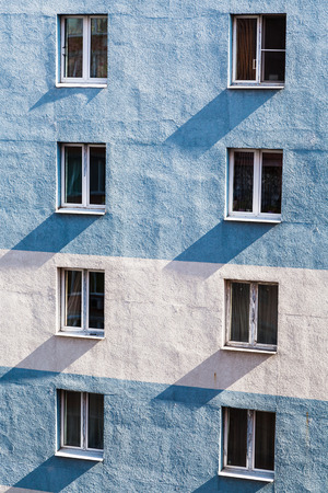 multistory: residential multistory building wall with windows illuminated by contrasting sunlight in morning