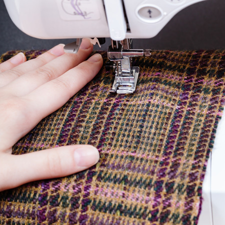 woolen cloth: sewer hand and foot of sewing machine on woolen cloth close up