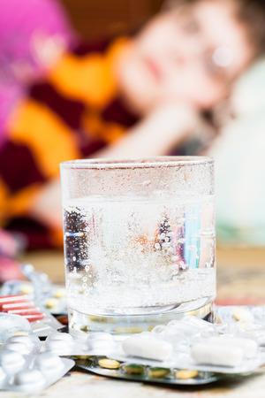 dissolved: vetro con medicamento disciolto in acqua e pila di pillole sul tavolo vicino e ragazza ammalata con la sciarpa intorno al collo sul divano in salotto su sfondo Archivio Fotografico