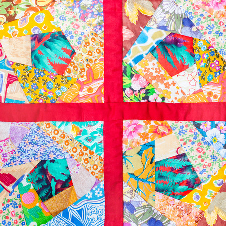 patchwork quilt: four details of hand made patchwork quilt framed in red cloth