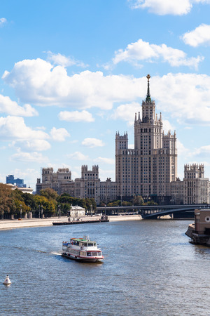 kotelnicheskaya embankment: Moscow cityscape - boat in Moskva river and view of Moskvoretskaya Embankment, Bolshoy Ustinsky Bridge and Kotelnicheskaya Embankment High-Rise Building in Moscow, Russia in summer day Editorial