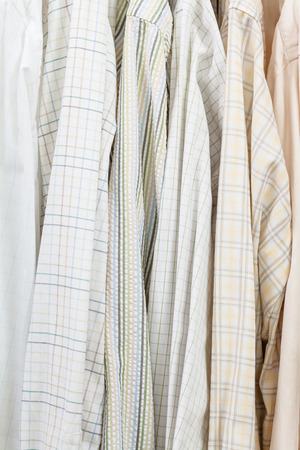 shirts on hangers: various male shirts on hangers in wardrobe close up Stock Photo