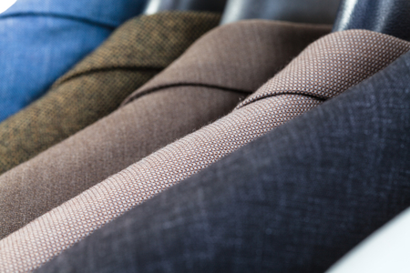 tailor suit: finished jackets on hangers in tailoring atelier close up Stock Photo