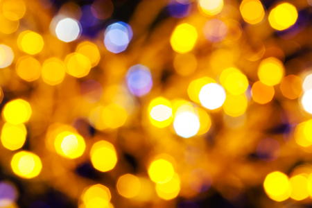 agleam: abstract blurred background - dark yellow and violet twinkling Christmas lights bokeh of electric garlands on Xmas tree