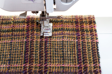 sartorial: foot of sewing machine on woolen textile close up