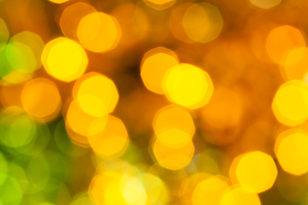 agleam: abstract blurred background - dark yellow and green shimmering Christmas lights bokeh of electric garlands on Xmas tree Stock Photo