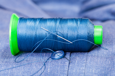 bobbin: tailoring still life - thread bobbin with needle, button on blue silk jacket