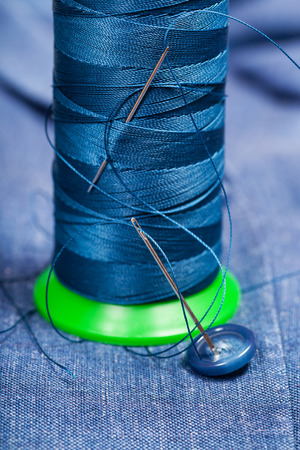 sartorial: tailoring still life - thread bobbin with needles, button on blue silk textile