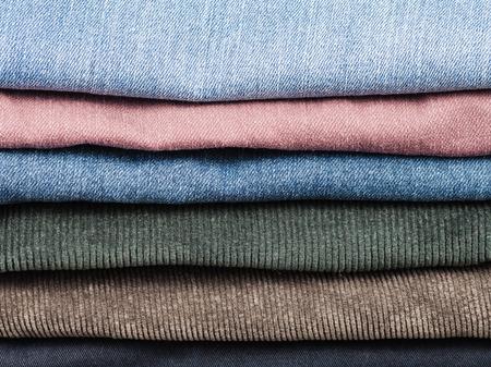 slacks: stack of various jeans and corduroy slacks close up Stock Photo