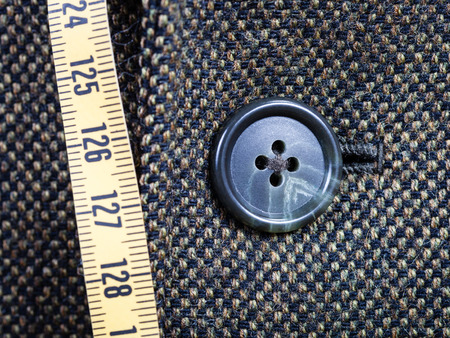 tailor measuring tape: tailor measuring tape and buttoned button on tweed jacket close up