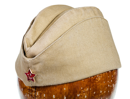 garrison: military green garrison cap with soviet red star sign on wooden dummy isolated on white background close up