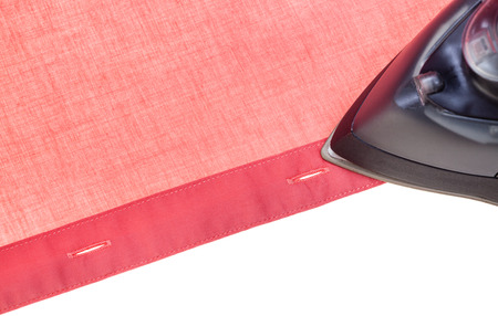sartorial: above view of black iron ironing red shirt isolated on white background
