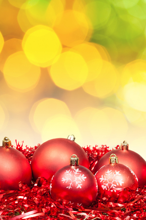 green christmas lights: Xmas still life - red baubles, tinsel with blurred yellow and green Christmas lights bokeh background Stock Photo