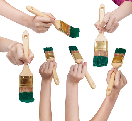 flat brushes: set of painter hands with flat paint brushes with green painted tips isolated on white background