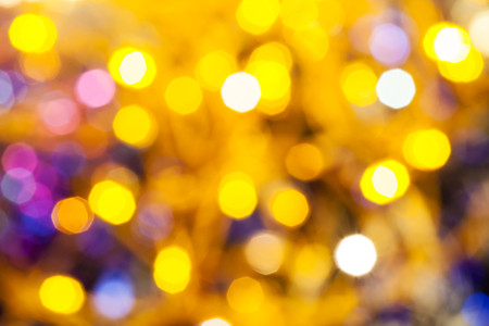 agleam: abstract blurred background - yellow and pink shimmering Christmas lights bokeh of electric garlands on Xmas tree Stock Photo