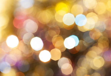 agleam: abstract blurred background - light brown shimmering Christmas lights bokeh of electric garlands on Xmas tree Stock Photo