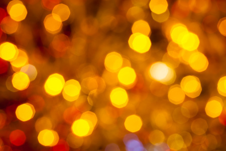 agleam: abstract blurred background - dark brown yellow and red shimmering Christmas lights bokeh of electric garlands on Xmas tree Stock Photo