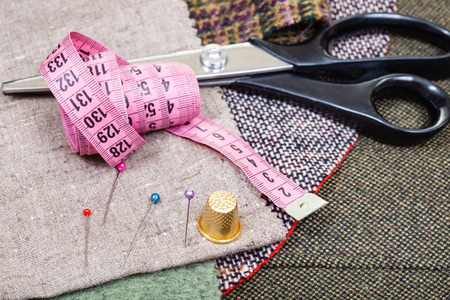 dressmaking still life - pink measure tape, pins, thimble, shears on fabrics