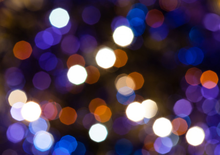 agleam: abstract blurred background - dark blue and violet shimmering Christmas lights bokeh of electric garlands on Xmas tree