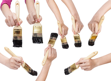 flat brushes: set of painter hands with flat paint brushes with black painted tips isolated on white background