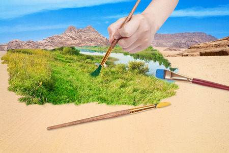 nature concept - seasons and weather changing: hand with paintbrush paints green meadow in sand desert