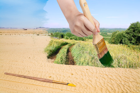 nature concept - seasons and weather changing: hand with paintbrush paints green countryside in sand desert Фото со стока