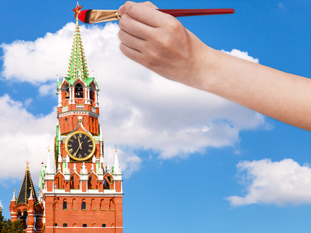 spasskaya: travel concept - hand with paintbrush paints the red star on Spasskaya tower on Moscow Kremlin
