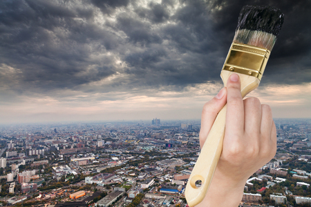 dark city: nature concept - hand with paintbrush paints storm clouds over dark city Stock Photo