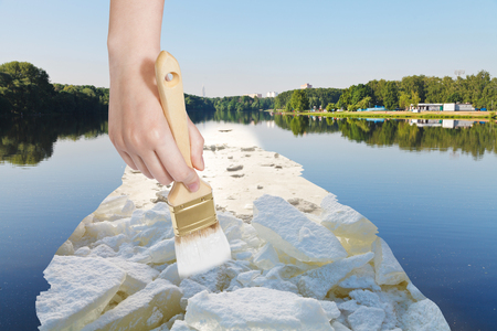 arise: nature concept - seasons and weather changing - hand with paintbrush paints ice blocks in lake in summer