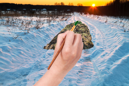 changing seasons: nature concept - seasons and weather changing: hand with paintbrush paints green plow land in winter snow road
