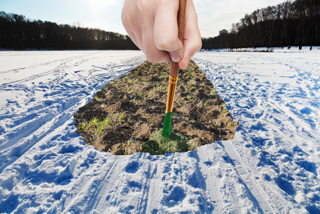 arise: nature concept - seasons and weather changing - hand with paintbrush paints spring plow ground in snow field Stock Photo