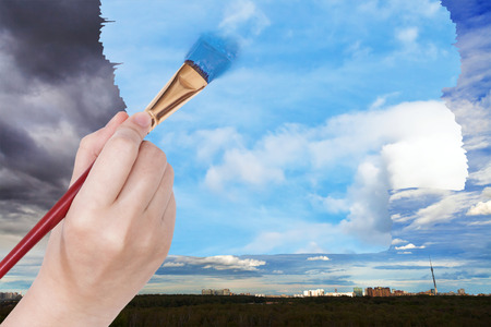 arise: nature concept - seasons and weather changing: hand with paintbrush paints blue sky on rainy clouds over city