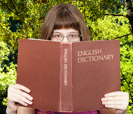 English dictionary: girl with spectacles looks over English Dictionary book with green summer forest on background
