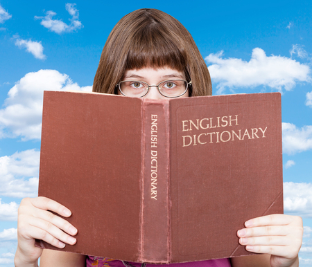 English dictionary: girl with spectacles looks over English Dictionary book with white clouds in blue sky on background