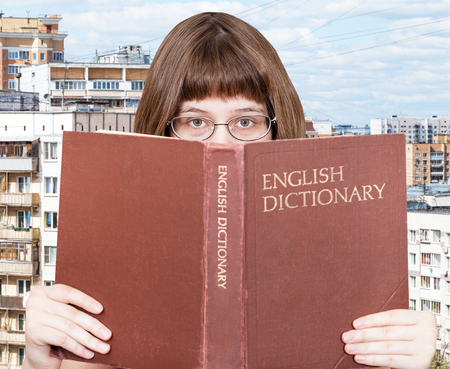 english dictionary: girl with spectacles looks over English Dictionary book with cityscape on background Stock Photo