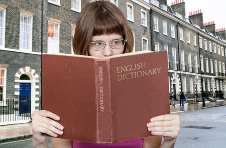 English dictionary: girl with spectacles reads English Dictionary book and typical London houses on background