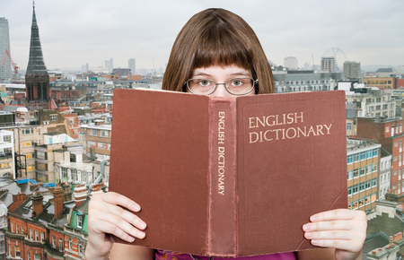 English dictionary: girl with spectacles looks over English Dictionary book and London skyline on background