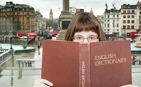 English dictionary: girl with spectacles looks over English Dictionary book and Trafalgar Square in London on background