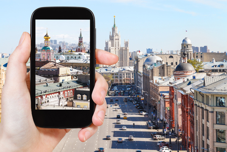 snapping fingers: travel concept - tourist photographs picture of Moscow street in historical center on smartphone Stock Photo