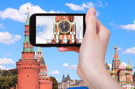spasskaya: travel concept - tourist photographs picture of clock on Spasskaya tower of Moscow Kremlin on smartphone Stock Photo