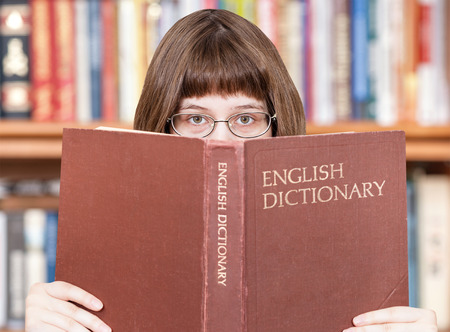 english dictionary: girl with spectacles looks over English Dictionary book and bookcase on background