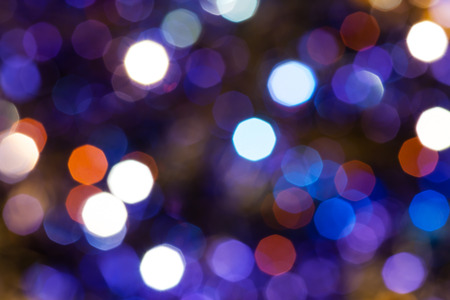 agleam: abstract blurred background - dark blue and violet twinkling Christmas lights bokeh of electric garlands on Xmas tree Stock Photo