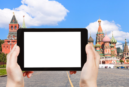 pokrovsky: travel concept - hand holds tablet pc with cut out screen and Vasilevsky descent of Red Square with Pokrovsky Cathedral on background