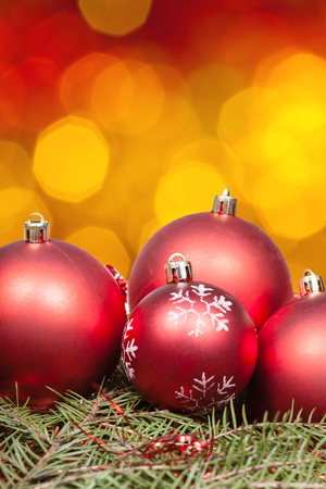 balls decorated: Xmas still life - red balls at green tree with blurred yellow, red, brown Christmas lights bokeh background Stock Photo