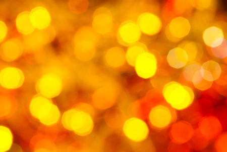 agleam: abstract blurred background - yellow and red flickering Christmas lights bokeh of electric garlands on Xmas tree Stock Photo
