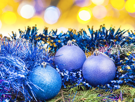xmas background: Xmas still life - blue balls, tinsel at green tree with blurred yellow Christmas lights bokeh background Stock Photo
