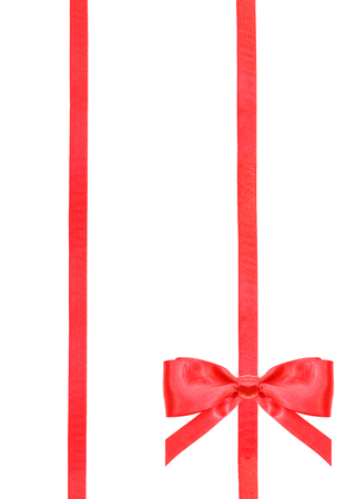 ribbon: one red satin bow in lower right corner and two vertical ribbons isolated on vertical white background