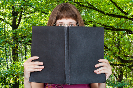 open book: girl with glasses looks over big book with blank cover and green woods on background