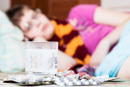 dissolved: glass with dissolved drug in water and pile of pills on table close up and sick girl with scarf around her neck on sofa in living room on background