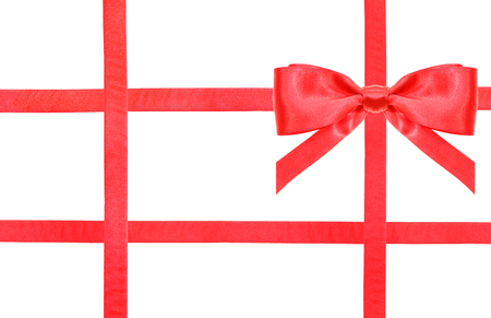 intersecting: one red satin bow in upper right corner and four intersecting ribbons isolated on horizontal white background Stock Photo